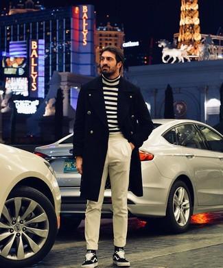 Cómo combinar: abrigo largo negro, jersey de cuello alto de rayas horizontales en blanco y negro, pantalón de vestir en beige, tenis de lona en negro y blanco