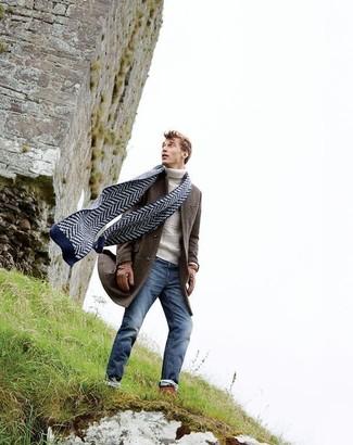 Cómo combinar: abrigo largo en marrón oscuro, jersey de cuello alto de punto blanco, vaqueros pitillo azules, bufanda en zig zag azul marino