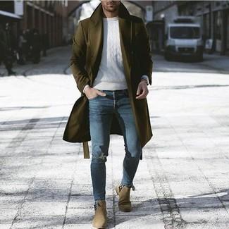 Cómo combinar: abrigo largo verde oliva, jersey de ochos blanco, vaqueros pitillo desgastados azules, botines chelsea de ante verde oliva