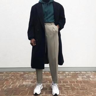 Cómo combinar: abrigo largo negro, sudadera con capucha verde oscuro, pantalón de vestir en beige, deportivas blancas