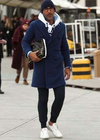 Cómo combinar: abrigo largo azul marino, sudadera con capucha estampada blanca, pantalón de chándal negro, tenis de cuero blancos