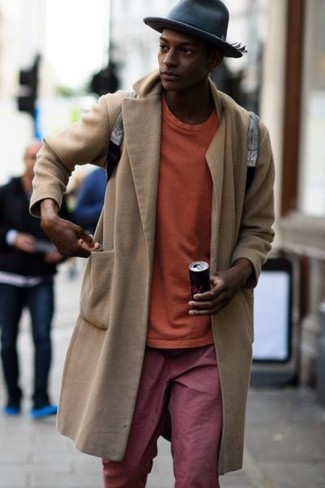 Cómo combinar: abrigo largo en beige, sudadera naranja, pantalón chino rojo, mochila de cuero gris