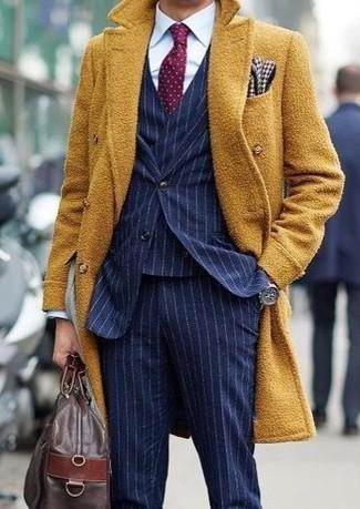 Cómo combinar: abrigo largo mostaza, traje de tres piezas de rayas verticales azul marino, camisa de vestir blanca, bolsa de viaje de cuero en marrón oscuro