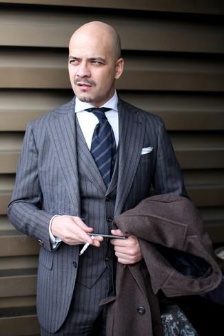 Cómo combinar: abrigo largo en marrón oscuro, traje de tres piezas de rayas verticales gris, camisa de vestir blanca, corbata de rayas verticales azul marino