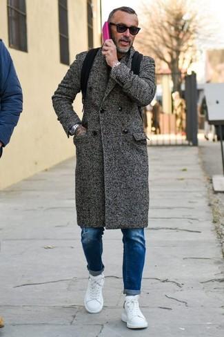 Cómo combinar: abrigo largo de espiguilla en gris oscuro, vaqueros pitillo desgastados azules, tenis de cuero blancos, mochila de lona negra