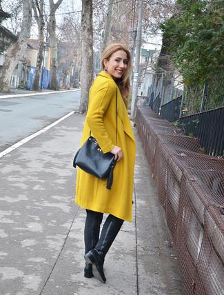 Cómo combinar: abrigo mostaza, botas sobre la rodilla de cuero negras, mochila con cordón de cuero negra, pendientes azules