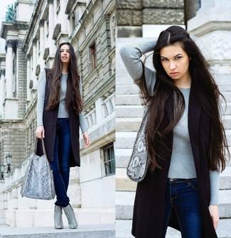 Cómo combinar: abrigo sin mangas negro, jersey con cuello circular gris, vaqueros pitillo azul marino, botines de cuero con print de serpiente grises