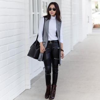 Cómo combinar: abrigo sin mangas gris, jersey de cuello alto blanco, vaqueros pitillo de cuero negros, botines de cuero en marrón oscuro