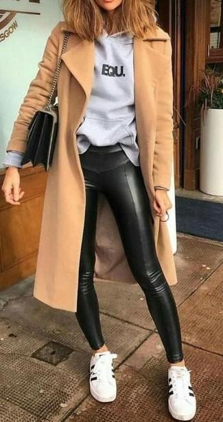 Cómo combinar: abrigo marrón claro, sudadera con capucha estampada gris, leggings de cuero negros, tenis de cuero en blanco y negro