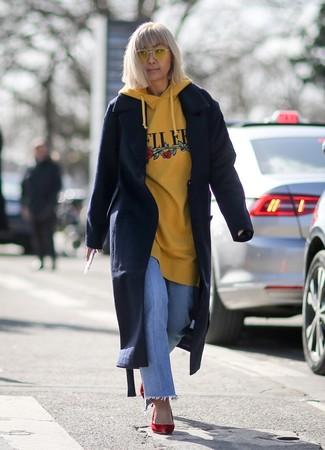 Cómo combinar: abrigo azul marino, sudadera con capucha estampada amarilla, vaqueros celestes, zapatos de tacón de ante rojos