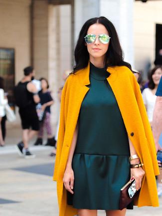 Cómo combinar: abrigo mostaza, vestido recto en verde azulado, cartera sobre burdeos, gafas de sol grises