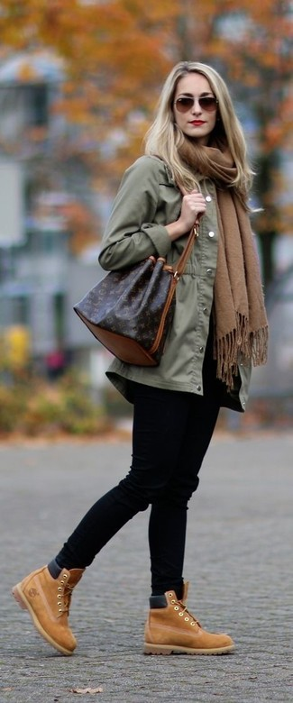 How to wear: olive anorak, black skinny jeans, tan suede lace-up ankle boots, dark brown leather bucket bag