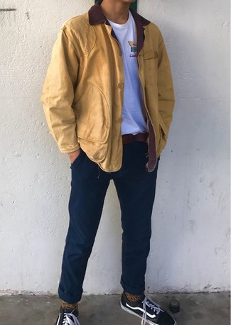How to wear: mustard barn jacket, white crew-neck t-shirt, navy chinos, black canvas low top sneakers