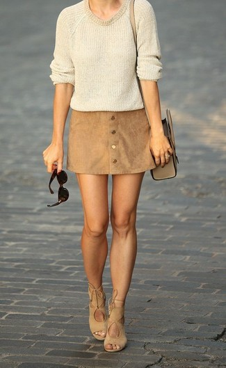 A cream crew-neck jumper and a button skirt are great staples that will integrate perfectly within your current looks. A cool pair of khaki suede heeled sandals is an easy way to upgrade your look. We promise this ensemble is the answer to all of your transitional style woes.