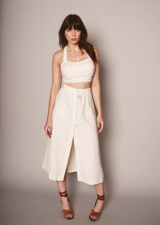 A beige cropped top and a button skirt is a good pairing to impress your crush on a date night. Dress up this look with tobacco suede heeled sandals. This outfit is great when it's super hot outside.