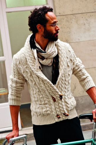 This combination of a cream knit duffel cardigan and vertical striped trousers is the picture of elegance.