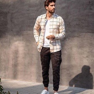 Men's Outfits 2020: For an off-duty outfit, pair a beige check long sleeve shirt with dark brown cargo pants — these items fit really well together. Introduce white canvas low top sneakers to the mix and the whole getup will come together.