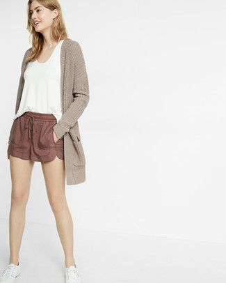 How to Wear Brown Shorts For Women: This is definitive proof that a beige knit open cardigan and brown shorts look awesome when paired up in a relaxed outfit. A pair of white low top sneakers serves as the glue that will bring this look together.