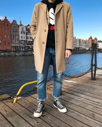 How to wear: beige overcoat, black print hoodie, blue jeans, black and white canvas high top sneakers