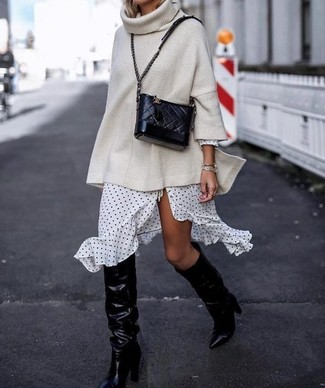 How to Wear White and Black Dress: Inject style into your day-to-day off-duty routine with white and black dress and a beige knit oversized sweater. Dial down the casualness of your ensemble by sporting a pair of black leather knee high boots.