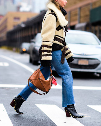 How to wear: beige shearling jacket, blue jeans, black studded leather ankle boots, tobacco leather tote bag