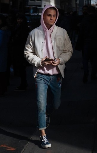 How to Wear Navy Canvas High Top Sneakers For Men: Team a beige varsity jacket with blue embroidered jeans if you seek to look casually cool without trying too hard. Why not complete your outfit with a pair of navy canvas high top sneakers for a more relaxed touch?