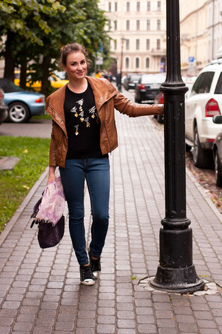 How to wear: tobacco leather biker jacket, black embellished crew-neck sweater, navy skinny jeans, black low top sneakers
