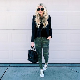 How to wear: black leather biker jacket, black crew-neck sweater, dark green camouflage sweatpants, white and black leather low top sneakers