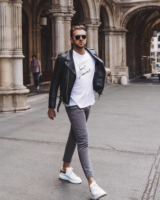 How to wear: black leather biker jacket, white and black crew-neck t-shirt, grey vertical striped chinos, white and black leather low top sneakers