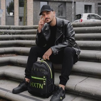 Black Canvas Backpack Outfits For Men: A black leather biker jacket and a black canvas backpack are the kind of a foolproof casual combo that you need when you have zero time to craft a look. Black leather low top sneakers will effortlessly lift up even the simplest ensemble.
