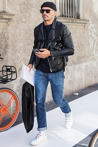 Fashion for Men Over 40: What To Wear: A black leather biker jacket and blue jeans are the perfect way to introduce played down dapperness into your off-duty routine. When it comes to footwear, this getup pairs perfectly with white leather low top sneakers.