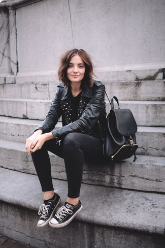 How to wear: black studded leather biker jacket, black crew-neck t-shirt, black skinny jeans, black and white canvas low top sneakers
