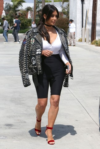 How to Wear a Black Studded Leather Biker Jacket For Women: A black studded leather biker jacket and black bike shorts are the kind of a winning off-duty combo that you so awfully need when you have zero time to dress up. Why not complete this look with red velvet heeled sandals for an extra touch of style?