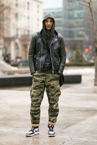 How to Wear Camouflage Pants In Chill Weather For Men: Opt for a black leather biker jacket and camouflage pants if you seek to look neat and relaxed without much effort. Complete your look with white and black leather high top sneakers to switch things up.