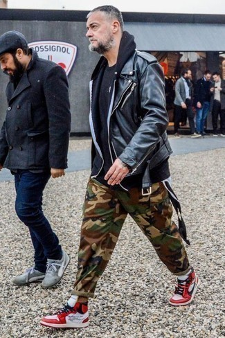 How to Wear Camouflage Pants For Men: Stay stylish on busy days by opting for a black leather biker jacket and camouflage pants. A pair of white and red leather high top sneakers instantly steps up the style factor of any getup.