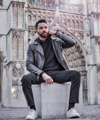 How to Wear a Black Leather Biker Jacket For Men: A black leather biker jacket and charcoal jeans teamed together are the ideal ensemble for men who prefer cool and casual looks. Complement this look with a pair of white canvas low top sneakers and ta-da: the look is complete.