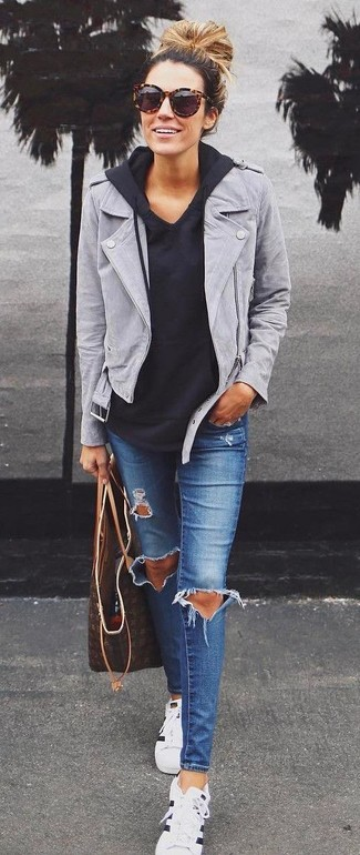 How to wear: grey suede biker jacket, black hoodie, blue ripped skinny jeans, white and black horizontal striped low top sneakers