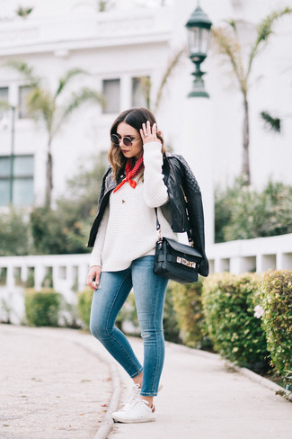 How to wear: black quilted leather biker jacket, white knit oversized sweater, blue skinny jeans, white low top sneakers