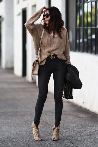 How to wear: black leather biker jacket, brown oversized sweater, black skinny jeans, beige suede lace-up ankle boots