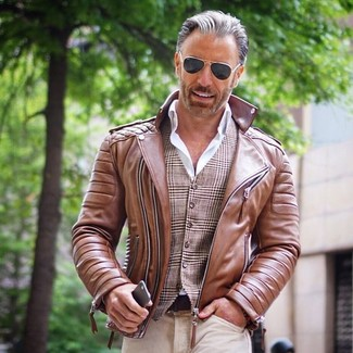 How to wear: brown leather biker jacket, brown plaid waistcoat, white dress shirt, beige jeans