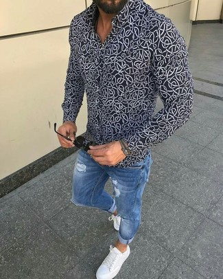 How to wear: black and white print dress shirt, blue ripped skinny jeans, white leather low top sneakers, black sunglasses