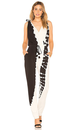 How to wear: black and white tie-dye jumpsuit, black suede heeled sandals, gold earrings