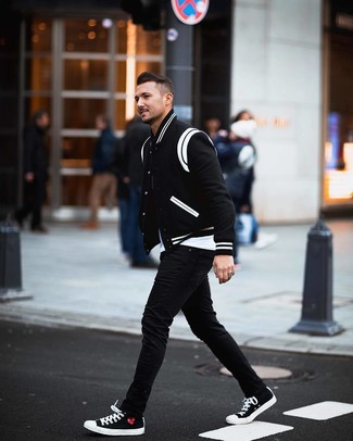 How to wear: black and white varsity jacket, white crew-neck t-shirt, black skinny jeans, black and white canvas low top sneakers