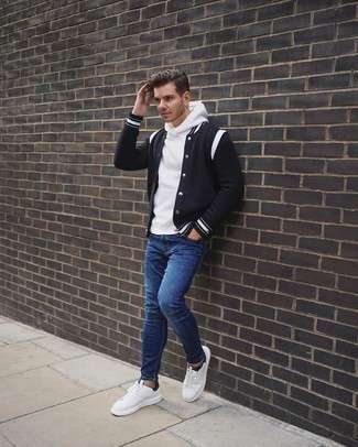 Blue Skinny Jeans Outfits For Men: A black and white varsity jacket and blue skinny jeans are great menswear items to have in the casual part of your closet. Finishing off with white and black canvas low top sneakers is an effective way to bring a little zing to this look.