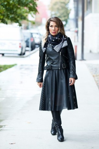How to wear: black leather biker jacket, black pleated leather midi skirt, black leather knee high boots, black and white print silk scarf