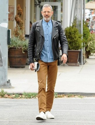 How to wear: black leather biker jacket, light blue chambray long sleeve shirt, brown chinos, white canvas low top sneakers
