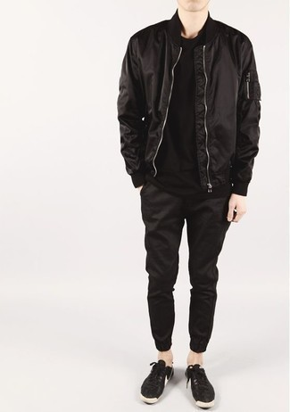 How to Wear Black Sweatpants In Fall Casually For Men: Opt for a black bomber jacket and black sweatpants for a practical getup that's also pulled together nicely. Black and white leather low top sneakers round off this outfit very nicely. This ensemble is a viable idea when it comes to an amazing transition ensemble.