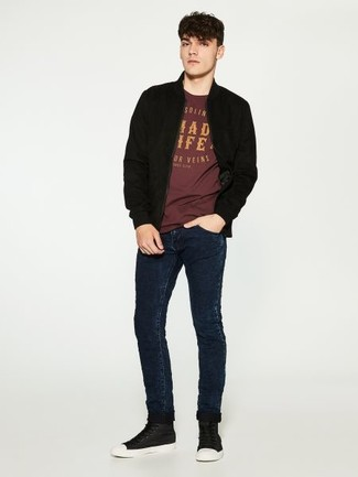 An oxblood crew-neck t-shirt and navy blue skinny jeans are absolute staples if you're planning an off-duty wardrobe that matches up to the highest style standards. For footwear go down the casual route with black leather high top sneakers. Nothing like a neat getup to cheer up a dreary fall afternoon.