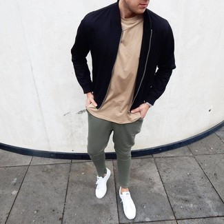 How to Wear a Black Bomber Jacket For Men: A black bomber jacket and olive sweatpants married together are a sartorial dream for those dressers who prefer casual ensembles. Complement your ensemble with white leather low top sneakers and ta-da: the ensemble is complete.