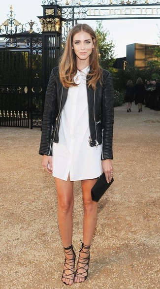 Pairing a black leather jacket with a white shirtdress is a comfortable option for running errands in the city. Dress up this look with black suede heeled sandals.